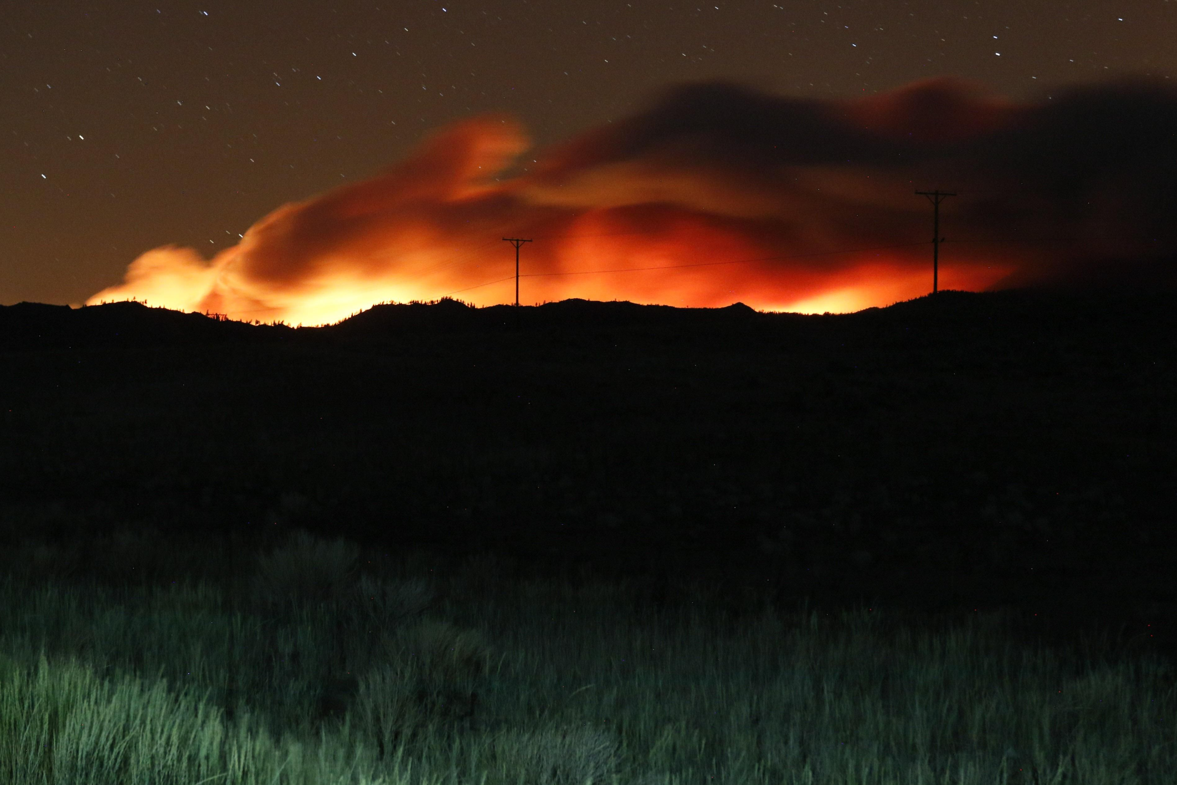 Flames illuminate the smoke rising from the Beckwourth complex fire. The Beckwourth Complex fire continues to burn through the night.