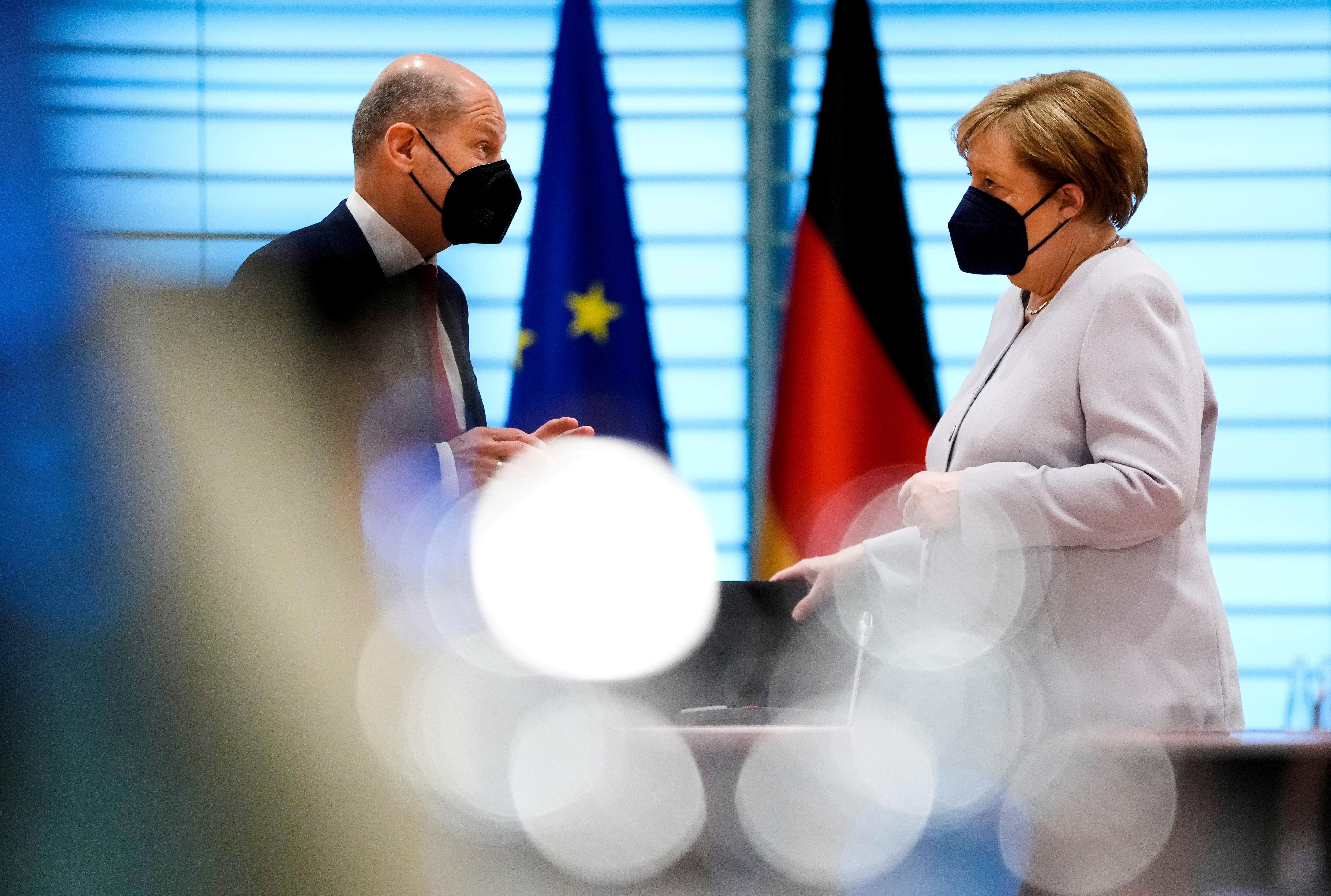German Chancellor Angela Merkel speaks with Finance Minister Olaf Scholz at the weekly cabinet meeting in Berlin, Germany June 9, 2021.