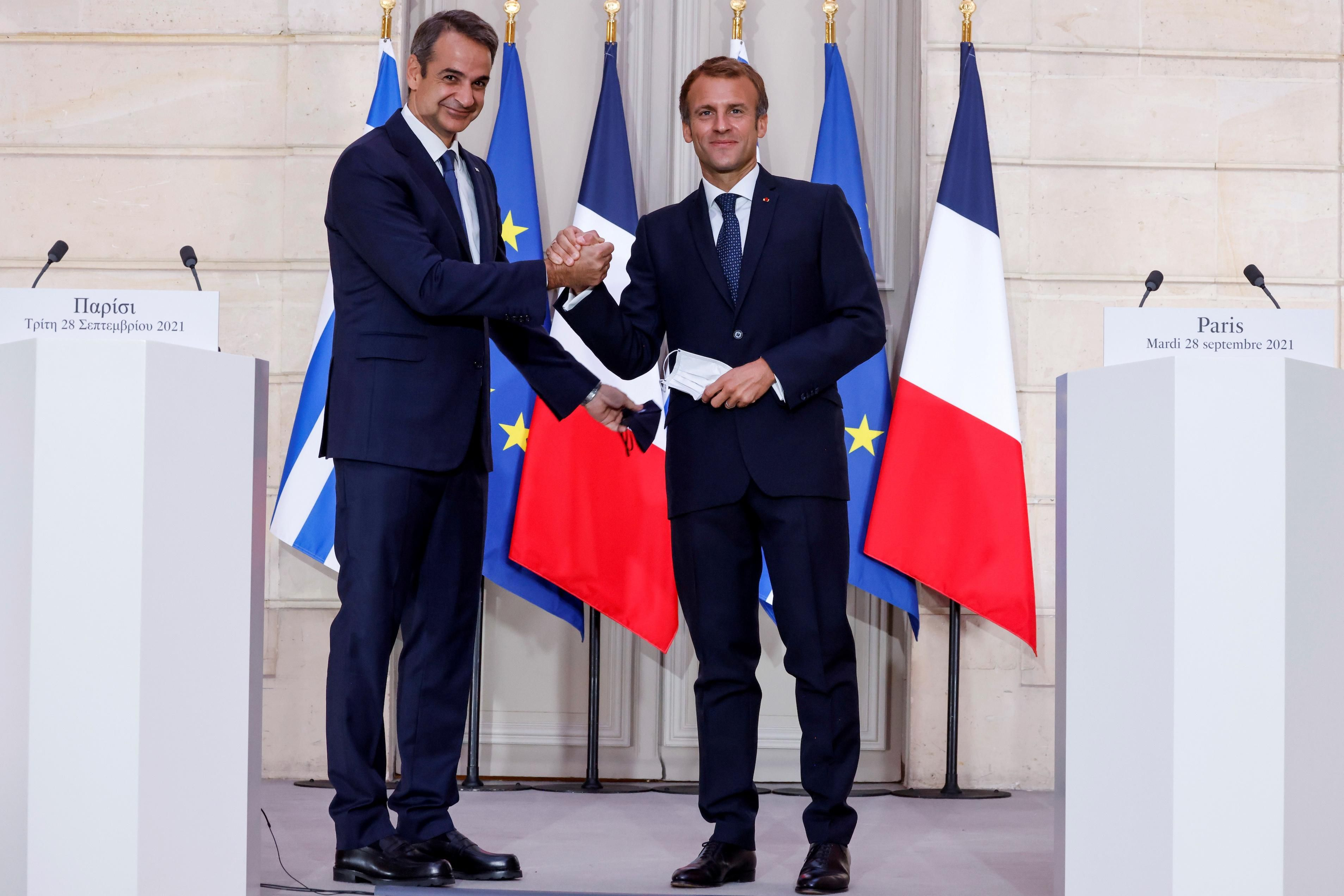 Greek Prime Minister Kyriakos Mitsotakis speaks as French President Emmanuel Macron listens on during a signing ceremony of a new defence deal at The Elysee Palace in Paris, France September 28, 2021.