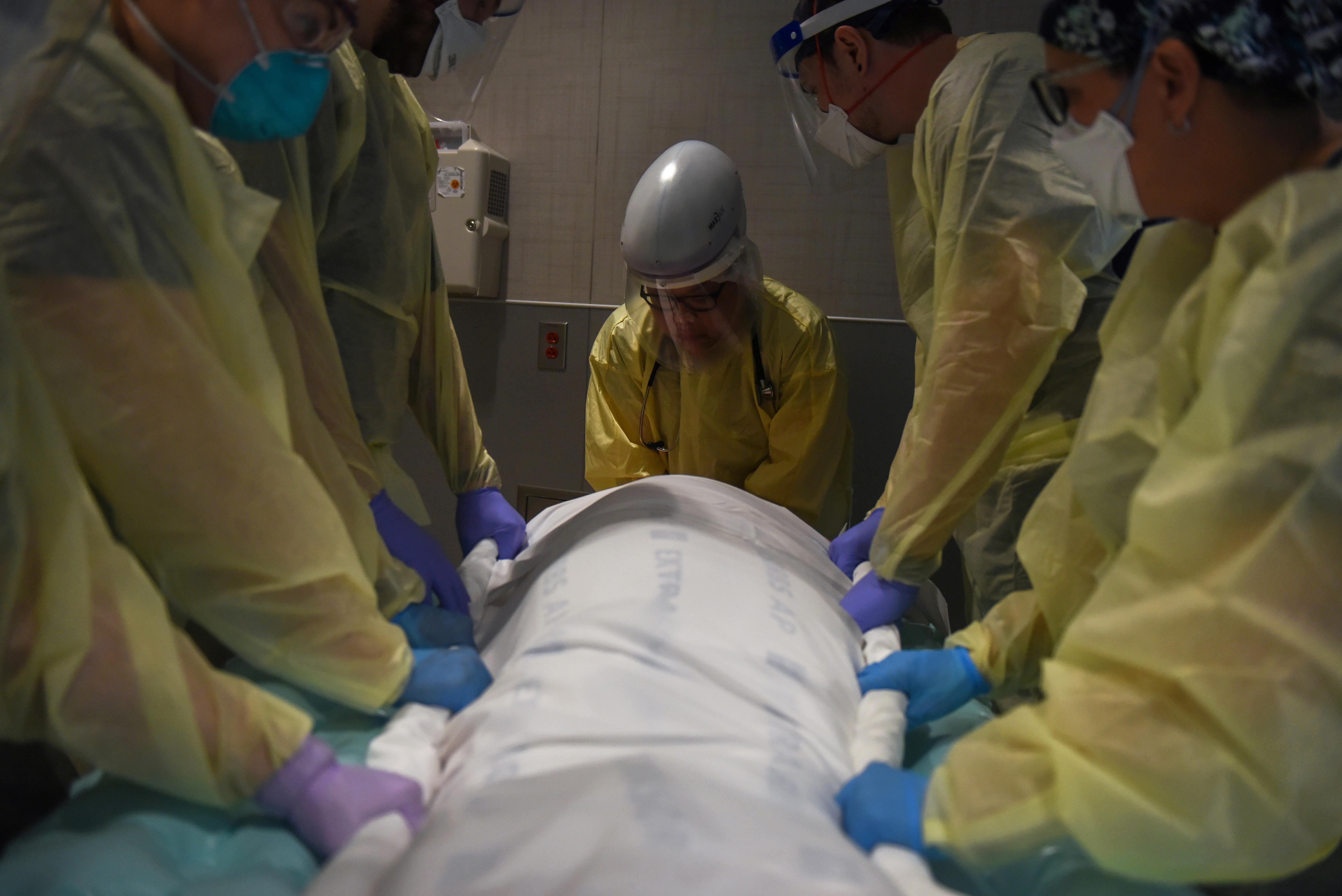 Healthcare personnel prepare to rotate a patient who is on a ventilator inside a room for patients with the coronavirus disease (COVID-19) at a hospital in Hutchinson, Kansas, U.S., November 20, 2020.