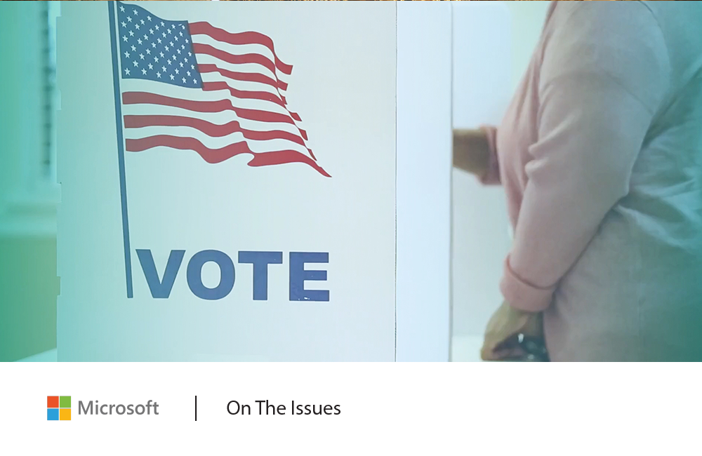 Image of a person voting at a voting booth decorated with an American flag