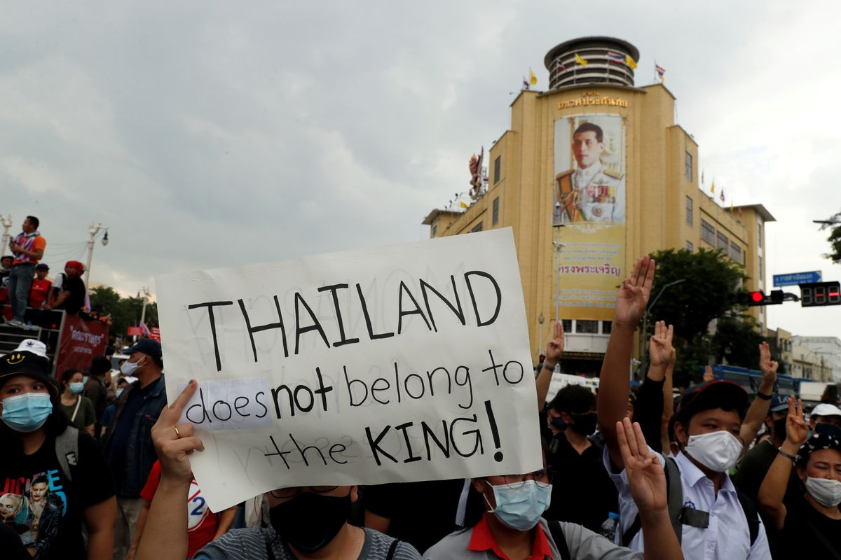 A pro-democracy demonstrator holds a placard past a portrait of Thai King Vajiralongkorn in Bangkok. Reuters