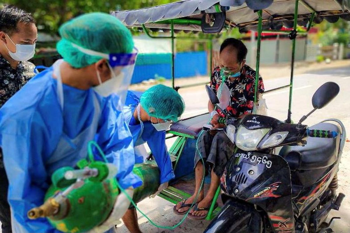 Volunteers help provide a coronavirus (COVID-19) patient with extra oxygen in the town of Kale, Sagaing Region, Myanmar, July 5, 2021. Picture taken July 5, 2021.
