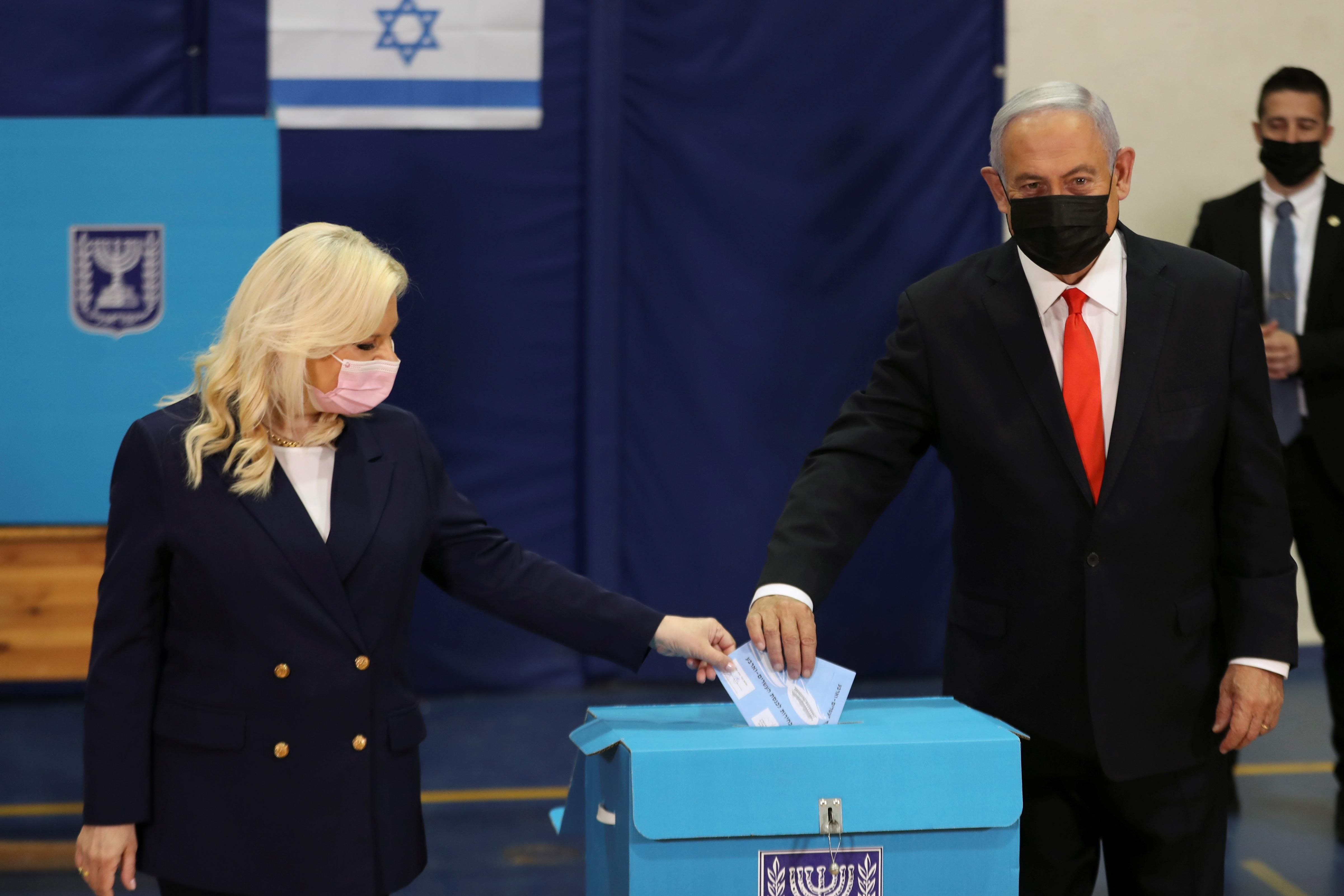 Israeli Prime Minister Benjamin Netanyahu and his wife Sara cast their ballots in Israel's general election, at a polling station in Jerusalem March 23, 2021