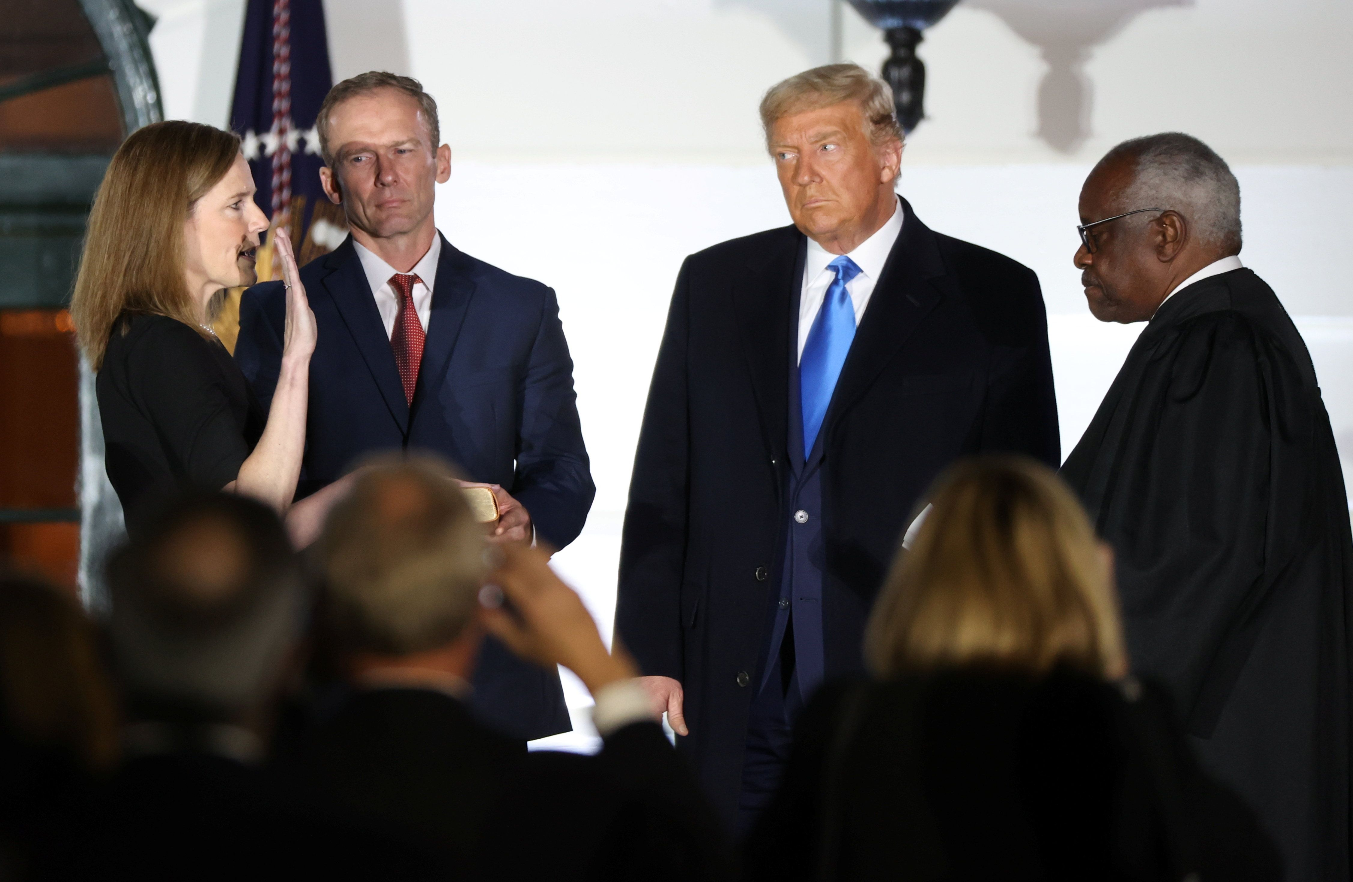 Judge Amy Coney Barrett is sworn in as an associate justice of the U.S. Supreme Court by Supreme Court Justice Clarence Thomas as her husband Jesse Barrett and President Donald Trump watch on the South Lawn of the White House in Washington, U.S., October 26, 2020