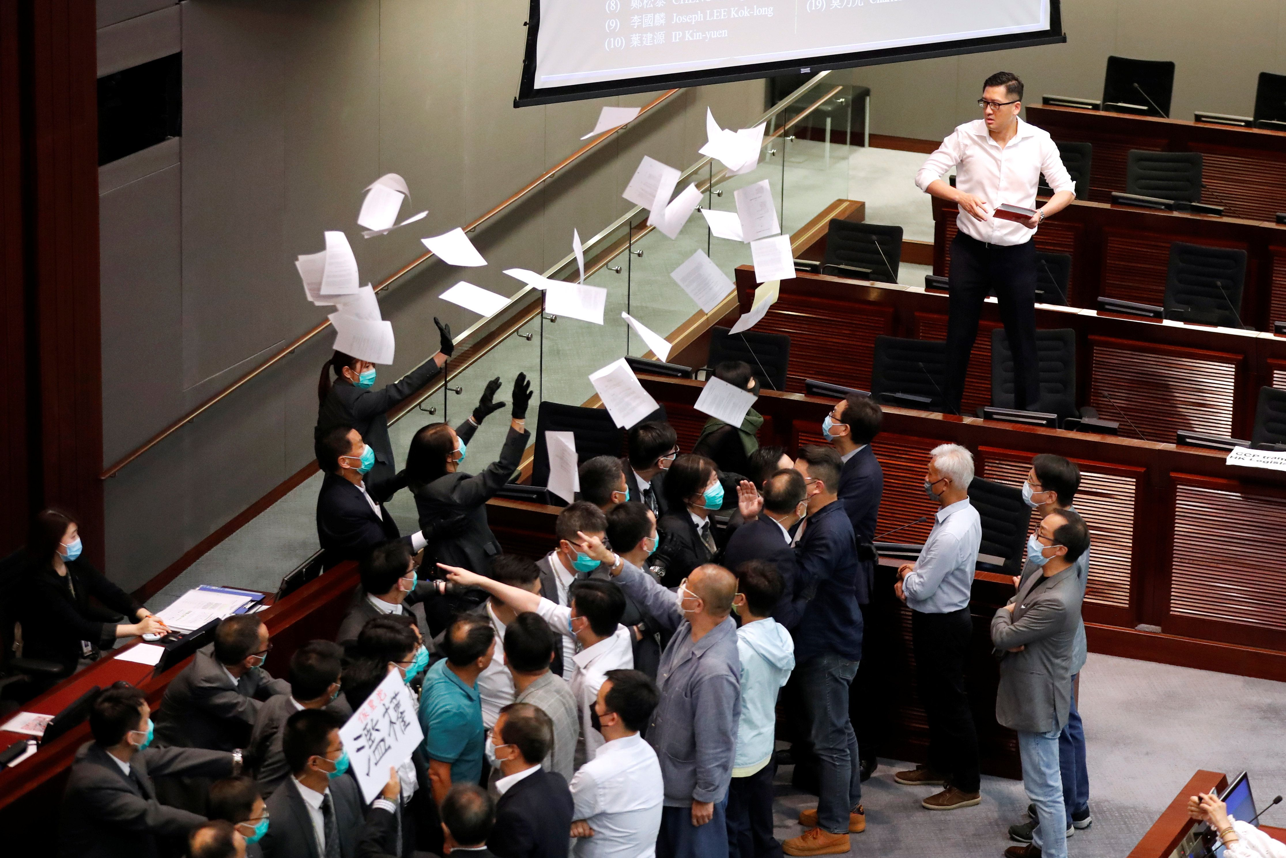 Mask-clad representatives in Hong Kong's legislature argue and throw papers in the air.