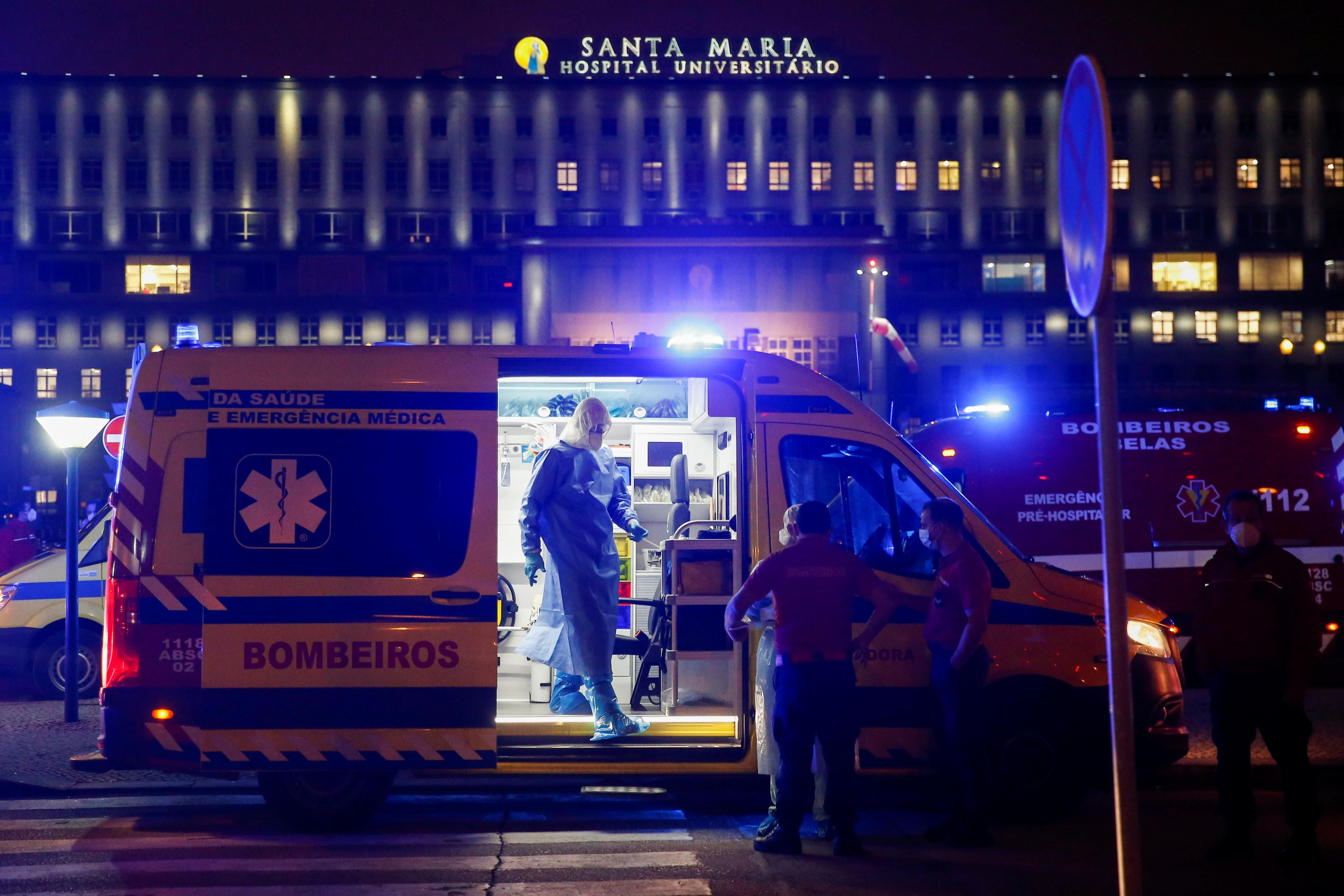 Medical personnel stand next to ambulances with COVID-19 patients as they wait in the queue at Santa Maria hospital, amid the coronavirus disease (COVID-19) pandemic in Lisbon, Portugal, January 27, 2021