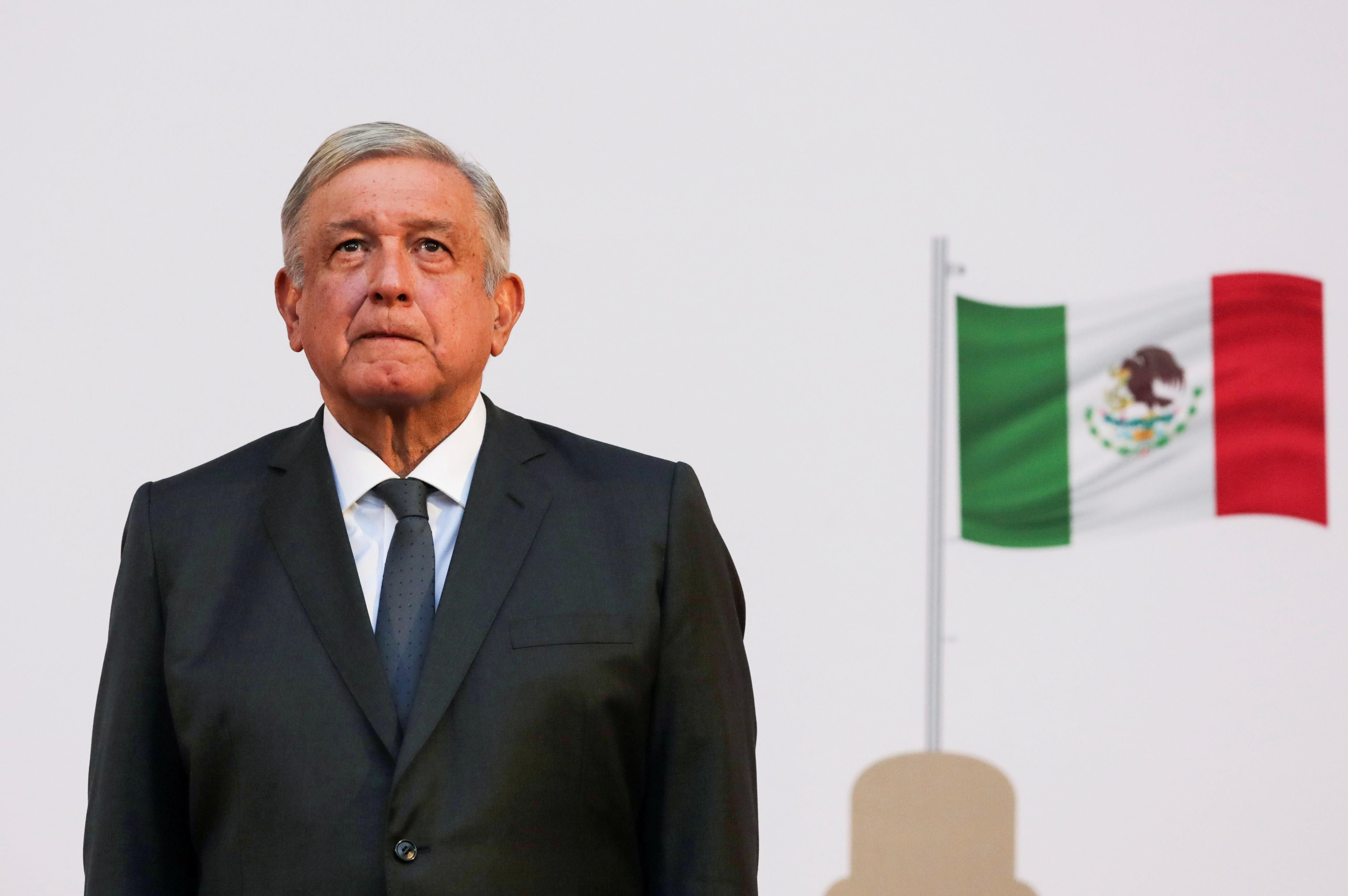 Mexico's president, Andres Manuel Lopez Obrador, listens to the national anthem after addressing the nation on his second anniversary as the President of Mexico, at the National Palace in Mexico City, Mexico, December 1, 2020.