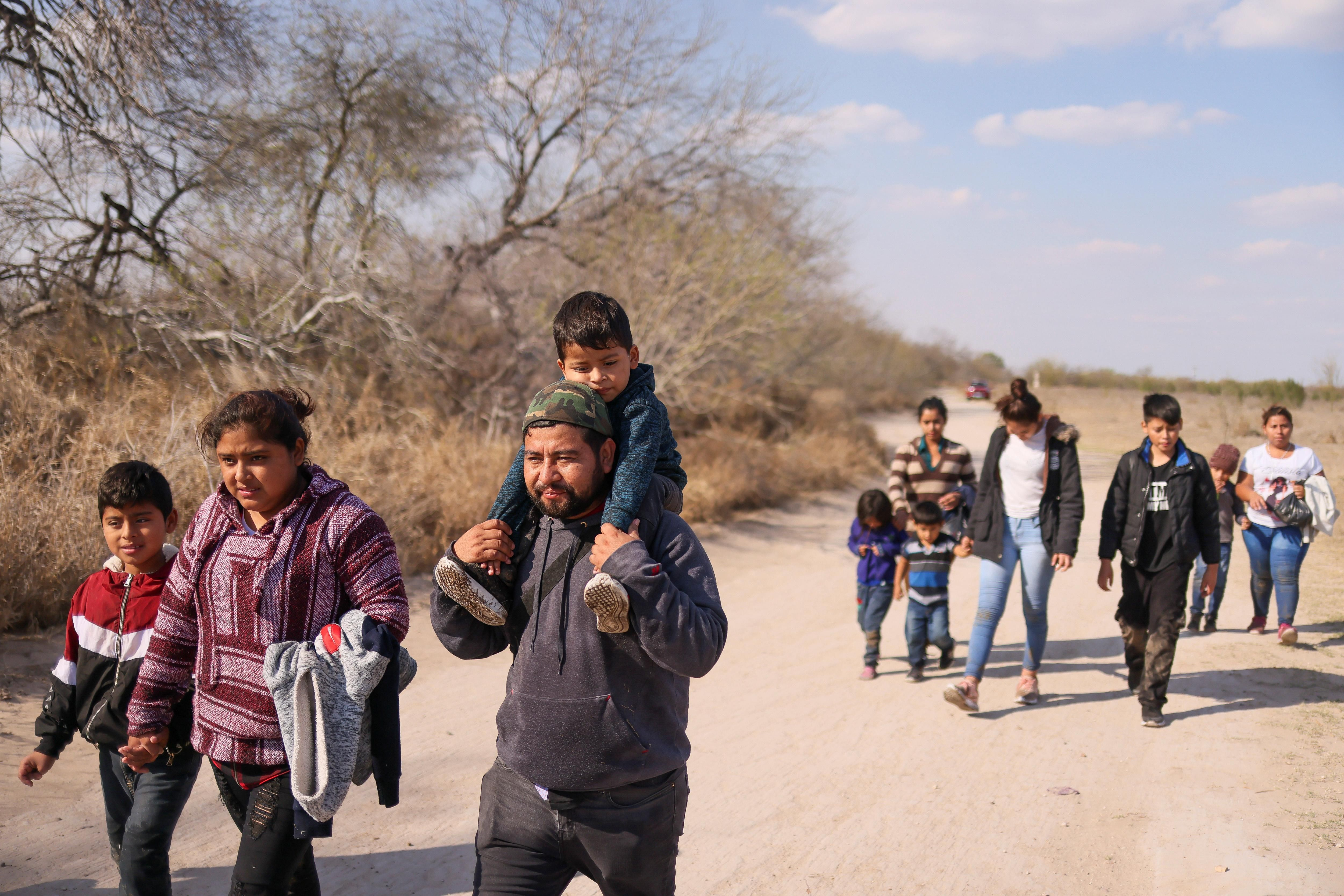 Migrant families with children walk along a dirt road after crossing the Rio Grande River into the United States from Mexico in Penitas, Texas, U.S., March 6, 2021.
