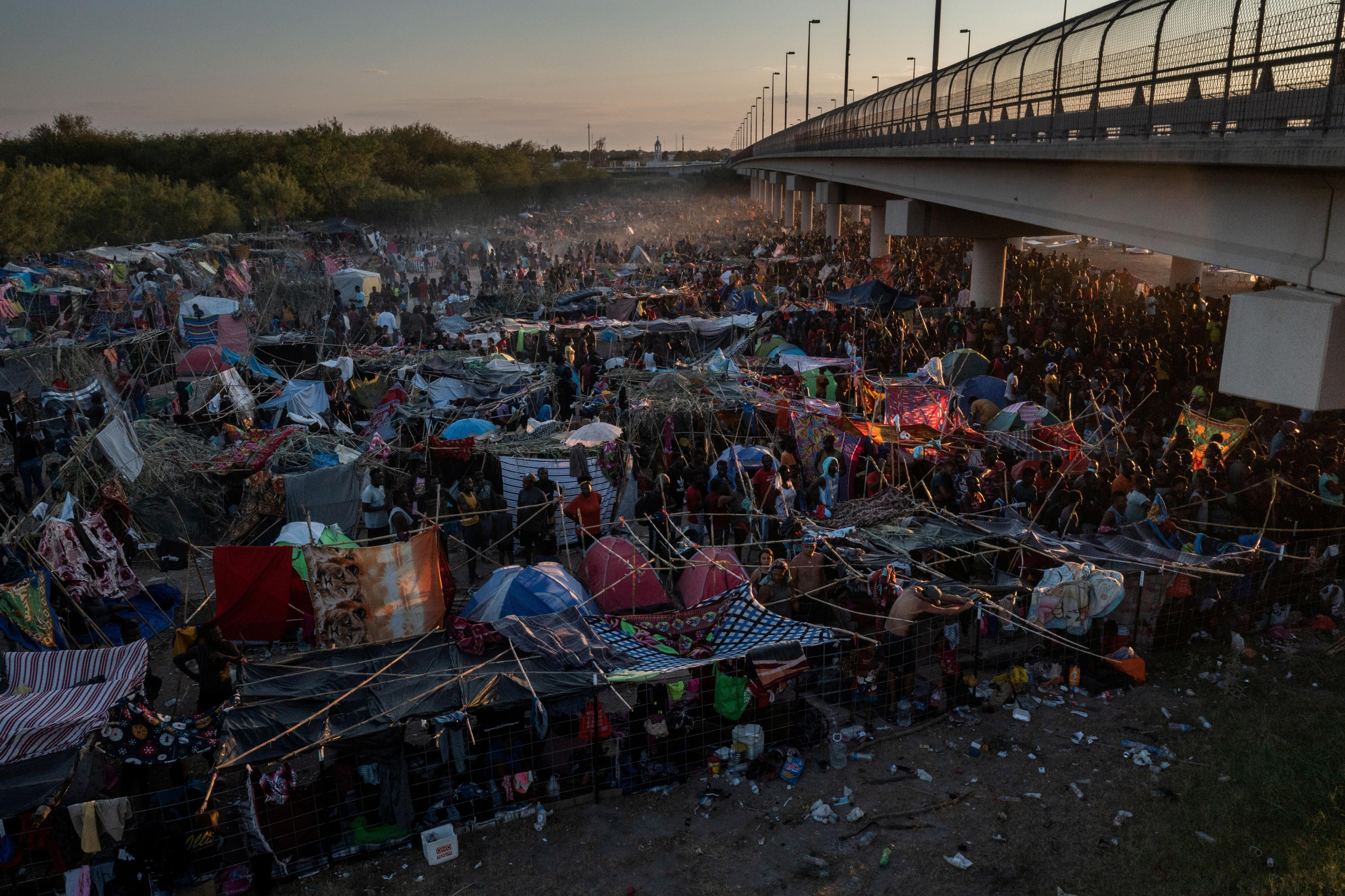 Migrants take shelter along the Del Rio International Bridge at sunset as they await to be processed after crossing the Rio Grande river into the U.S. from Ciudad Acuna in Del Rio, Texas, U.S. September 19, 2021.