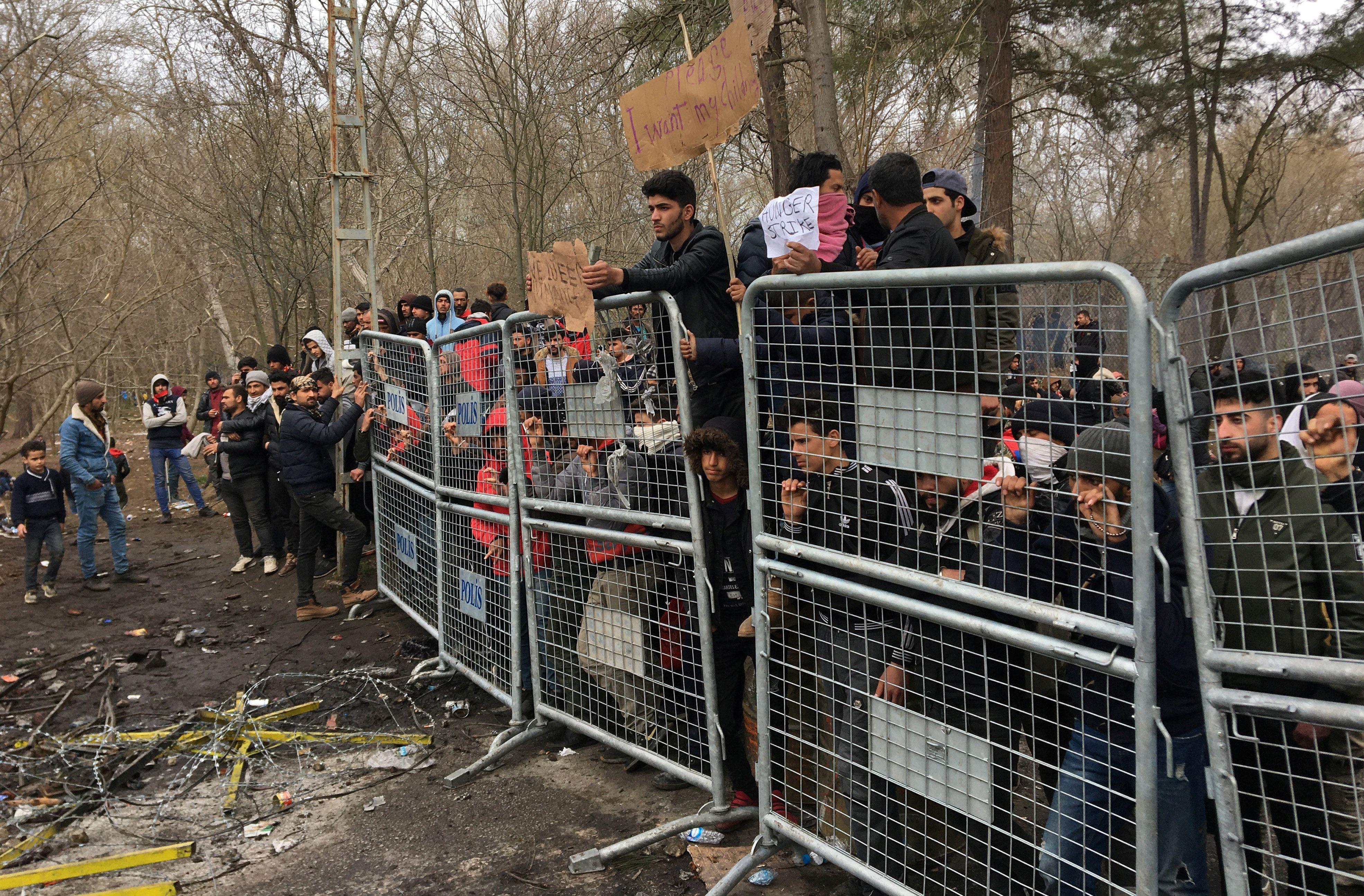 Migrants wait on at Turkey's Pazarkule border crossing with Greece's Kastanies. Reuters