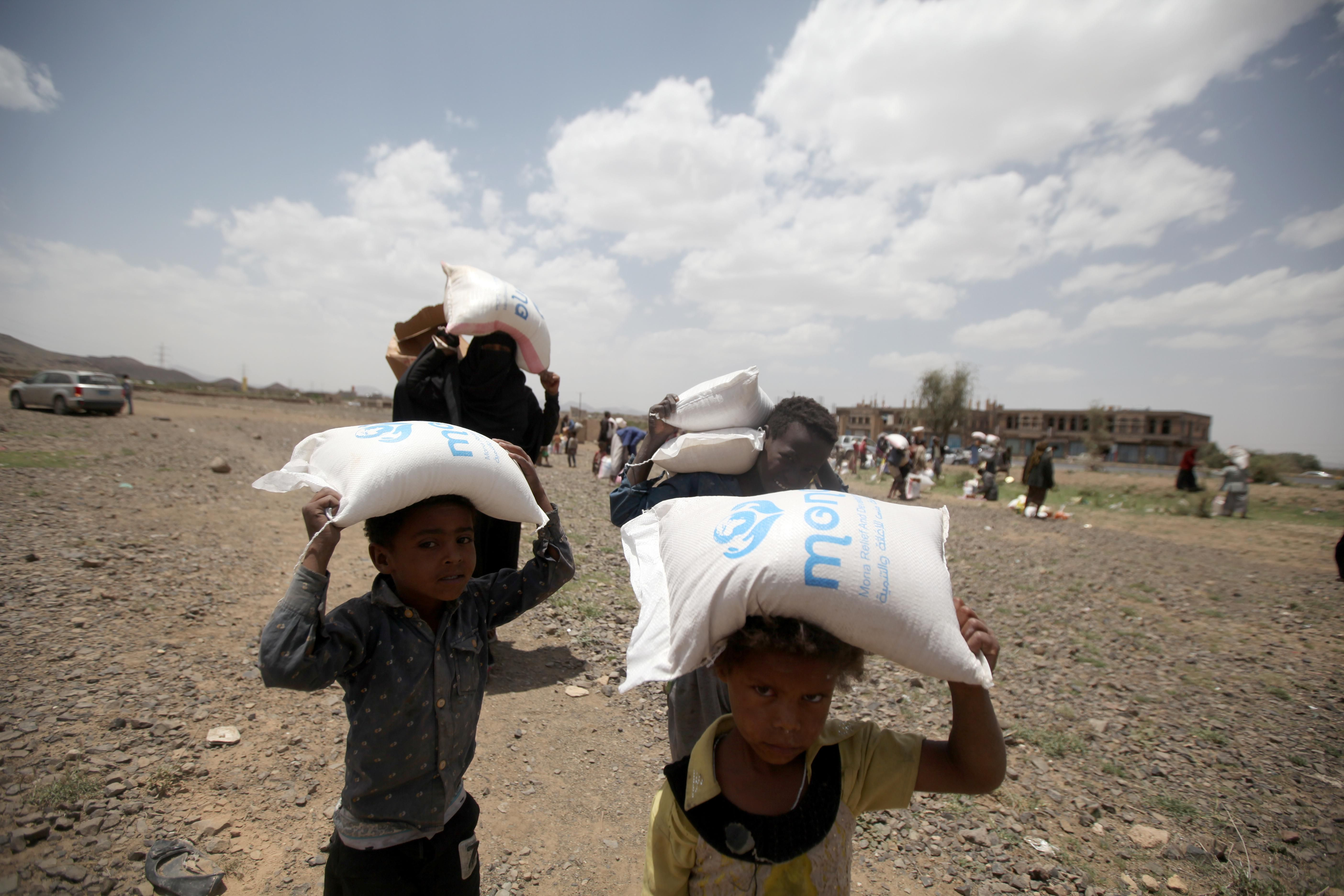 People carry food aid they received on the outskirts of Sanaa, Yemen.