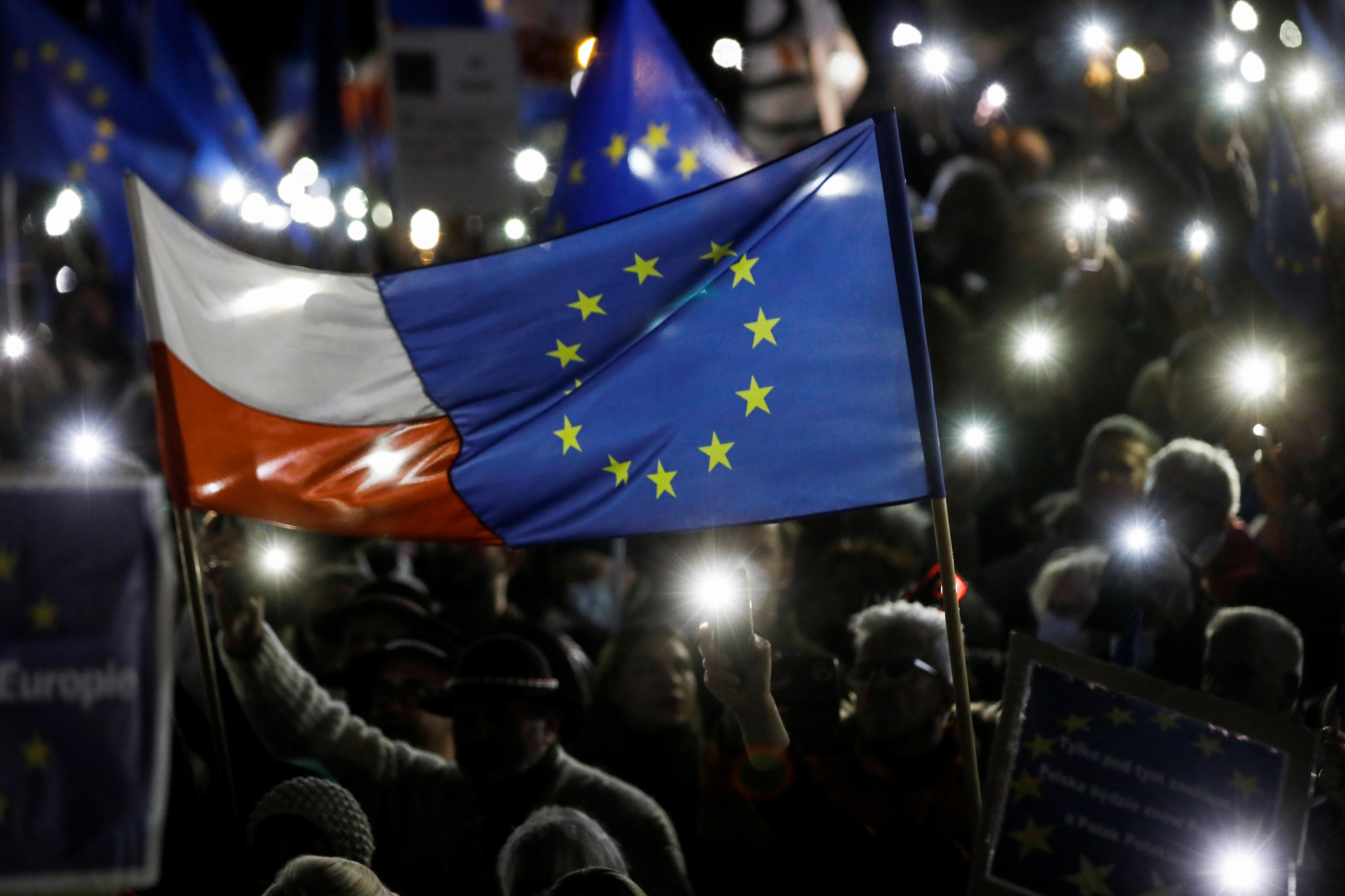 People hold flags and light up their mobile phones during a rally in support of Poland's membership in the European Union after the country's Constitutional Tribunal ruled on the primacy of the constitution over EU law, undermining a key tenet of European integration, in Warsaw, Poland, October 10, 2021.