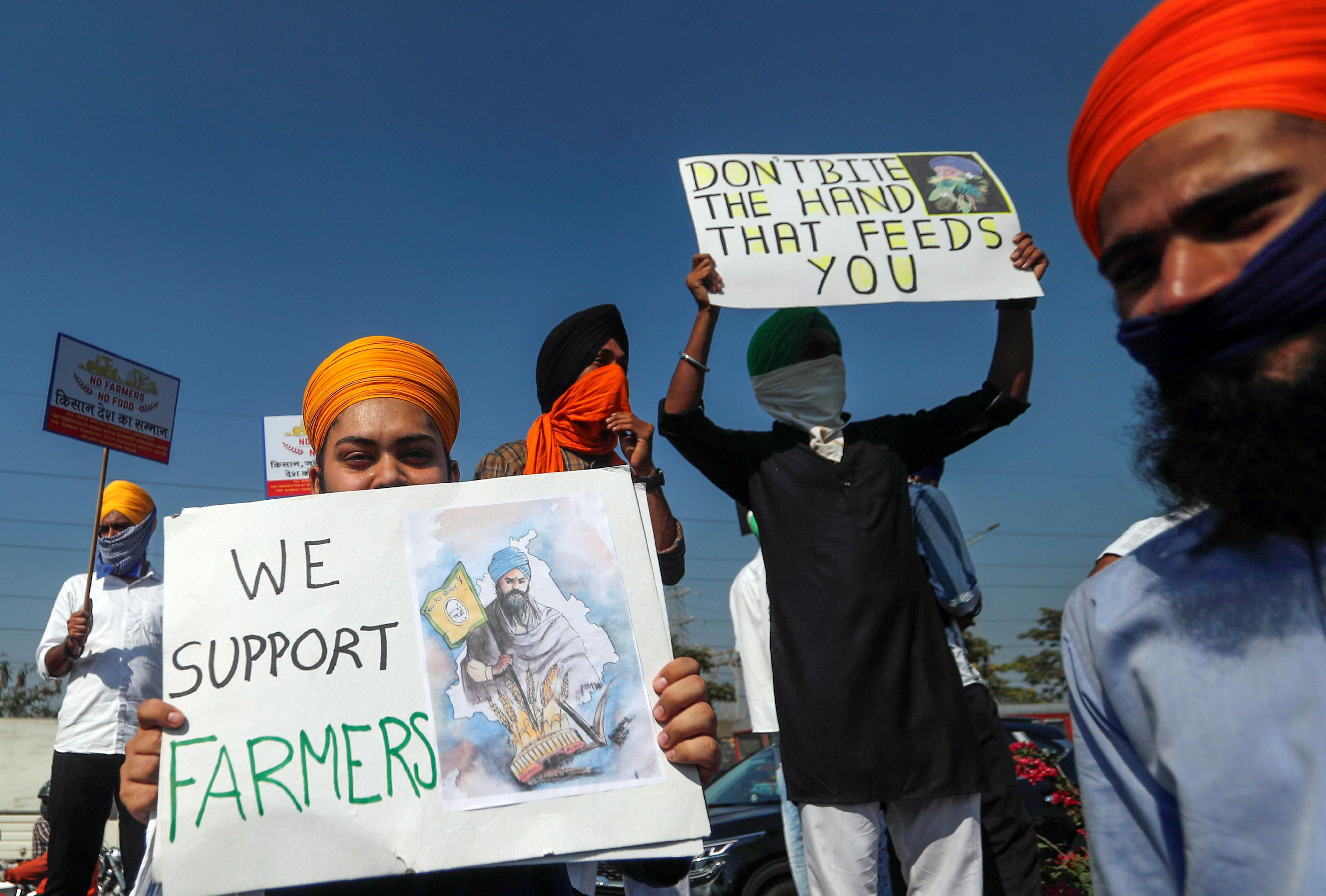 People hold placards during a nationwide strike to protest against newly passed farm bills, in Mumbai, India