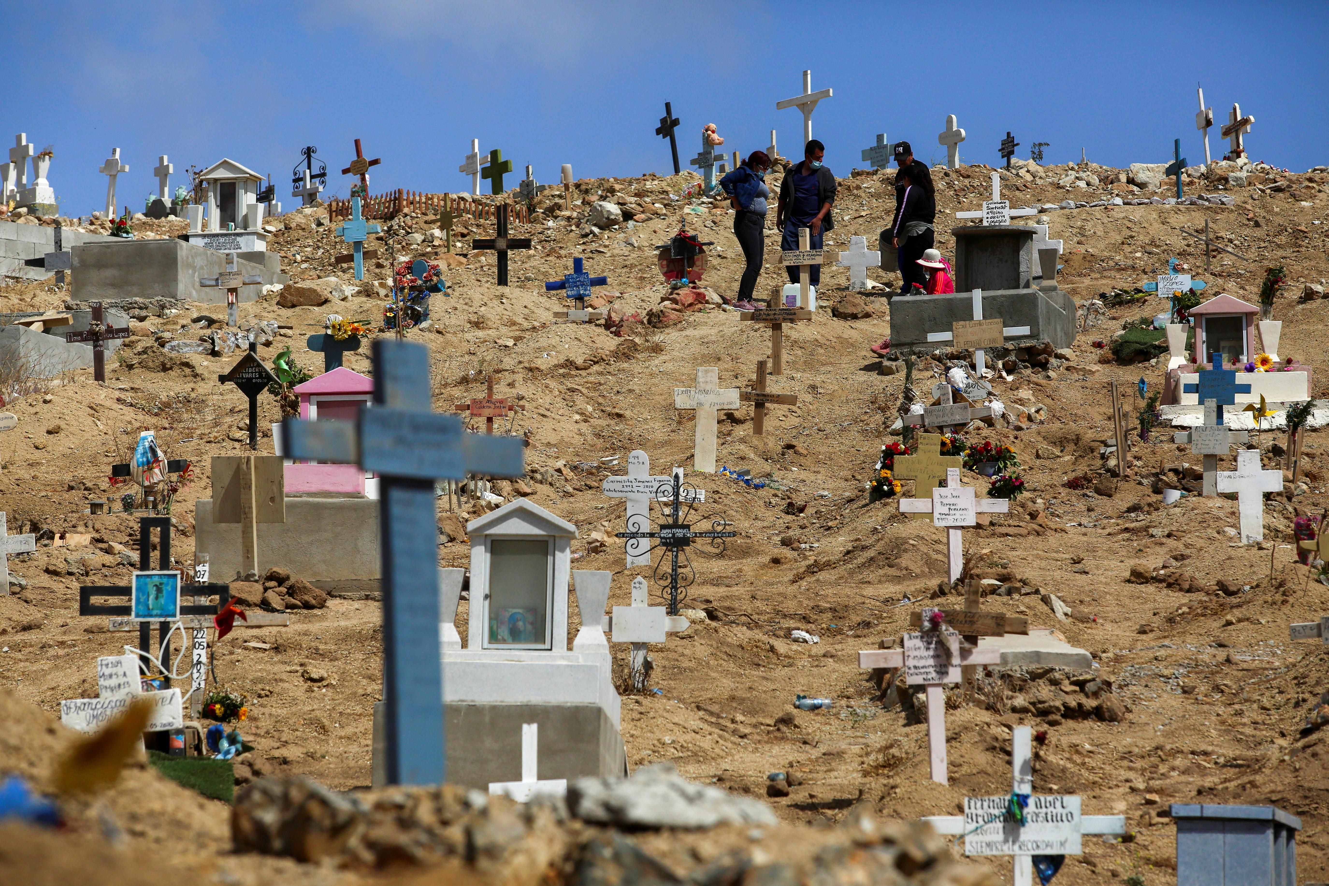 People stand among graves of victims of the coronavirus disease (COVID-19), and of others, at the municipal cemetery No. 12 in Tijuana, Mexico May 21, 2021