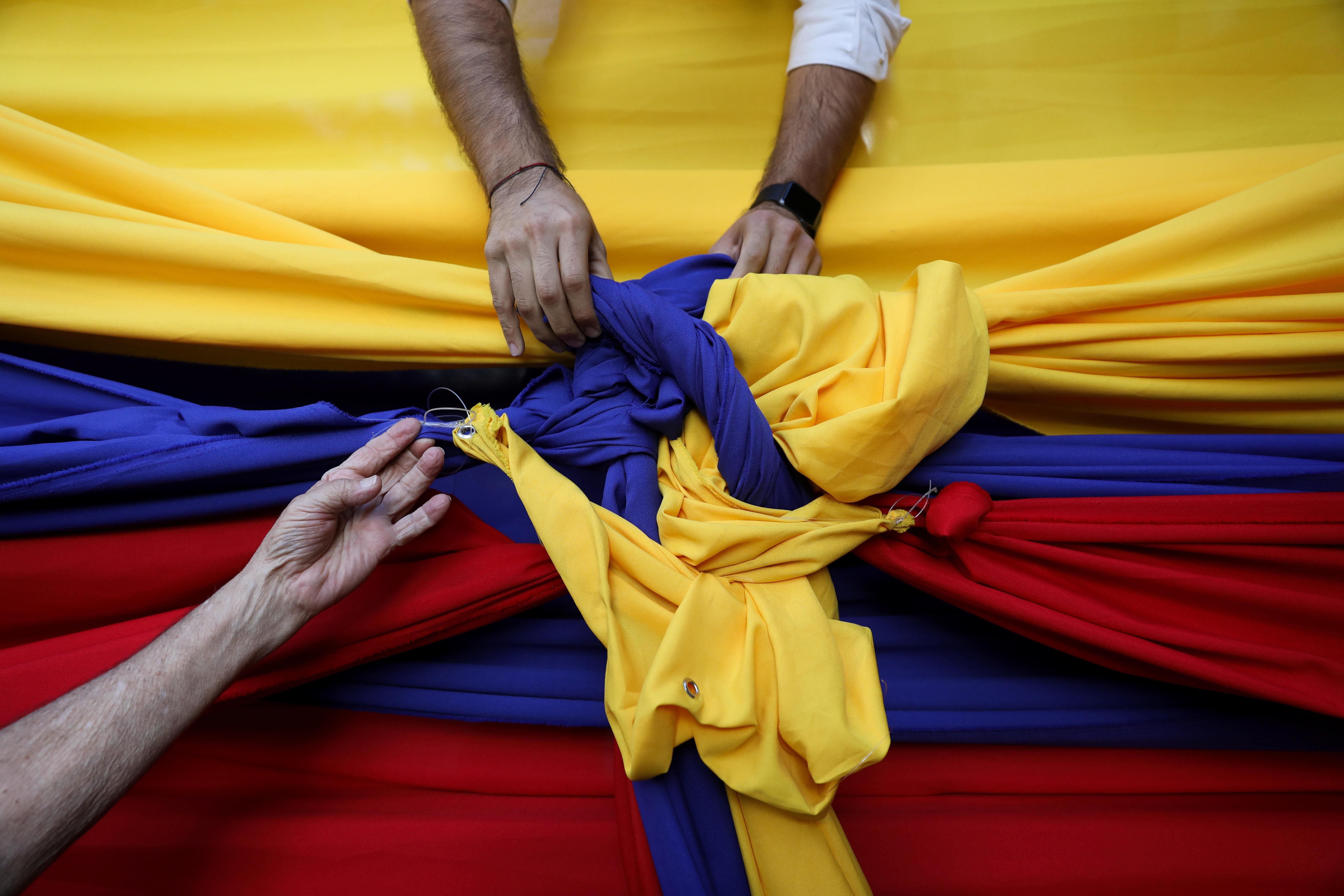 People untie cloth tarps with colors of the Venezuelan flag after a citizen assembly with Juan Guaidó, speaker of the National Assembly, in Caracas. Reuters