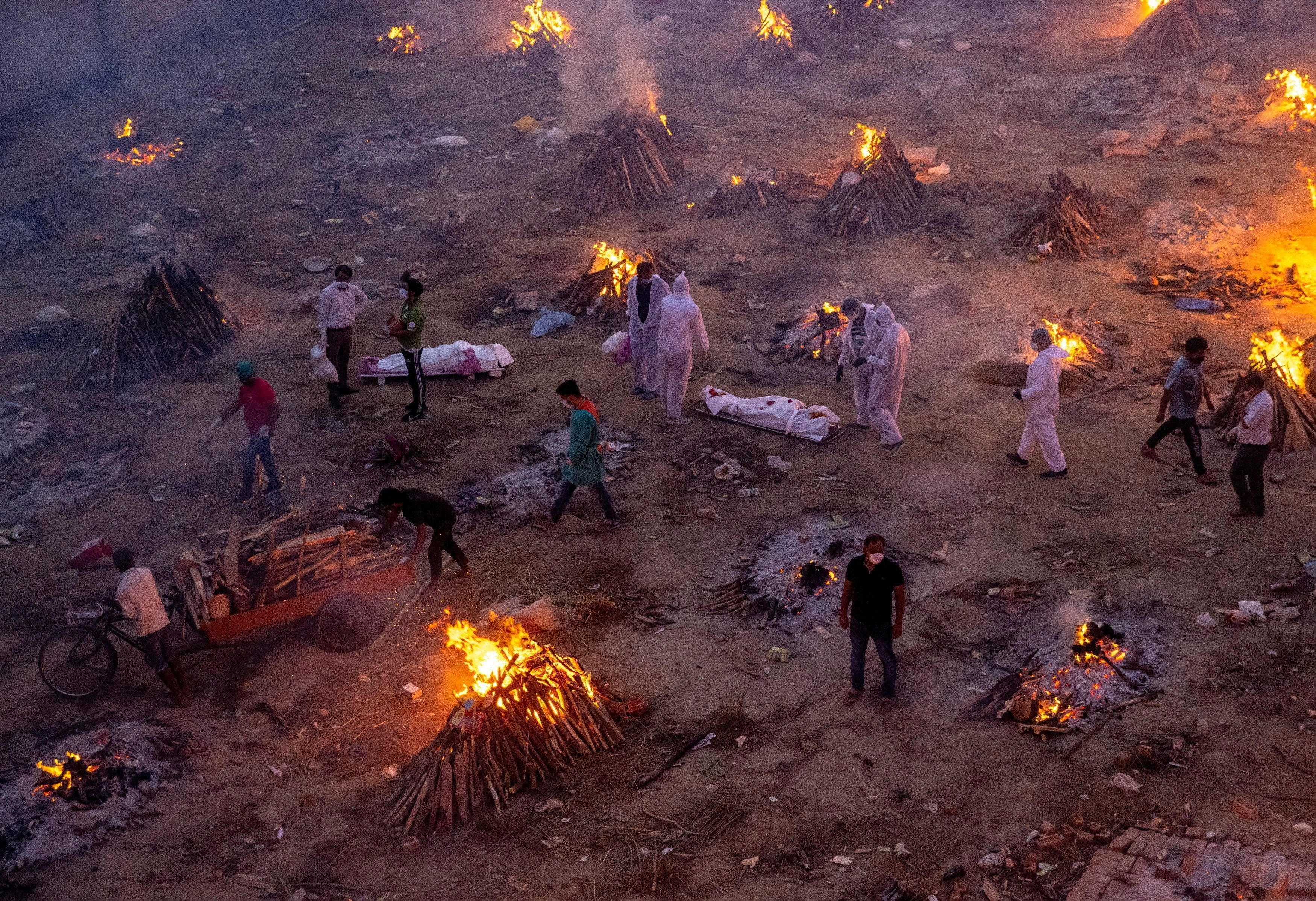 People wait to cremate victims who died due to the coronavirus disease (COVID-19), at a crematorium ground in New Delhi, India, April 23, 2021.
