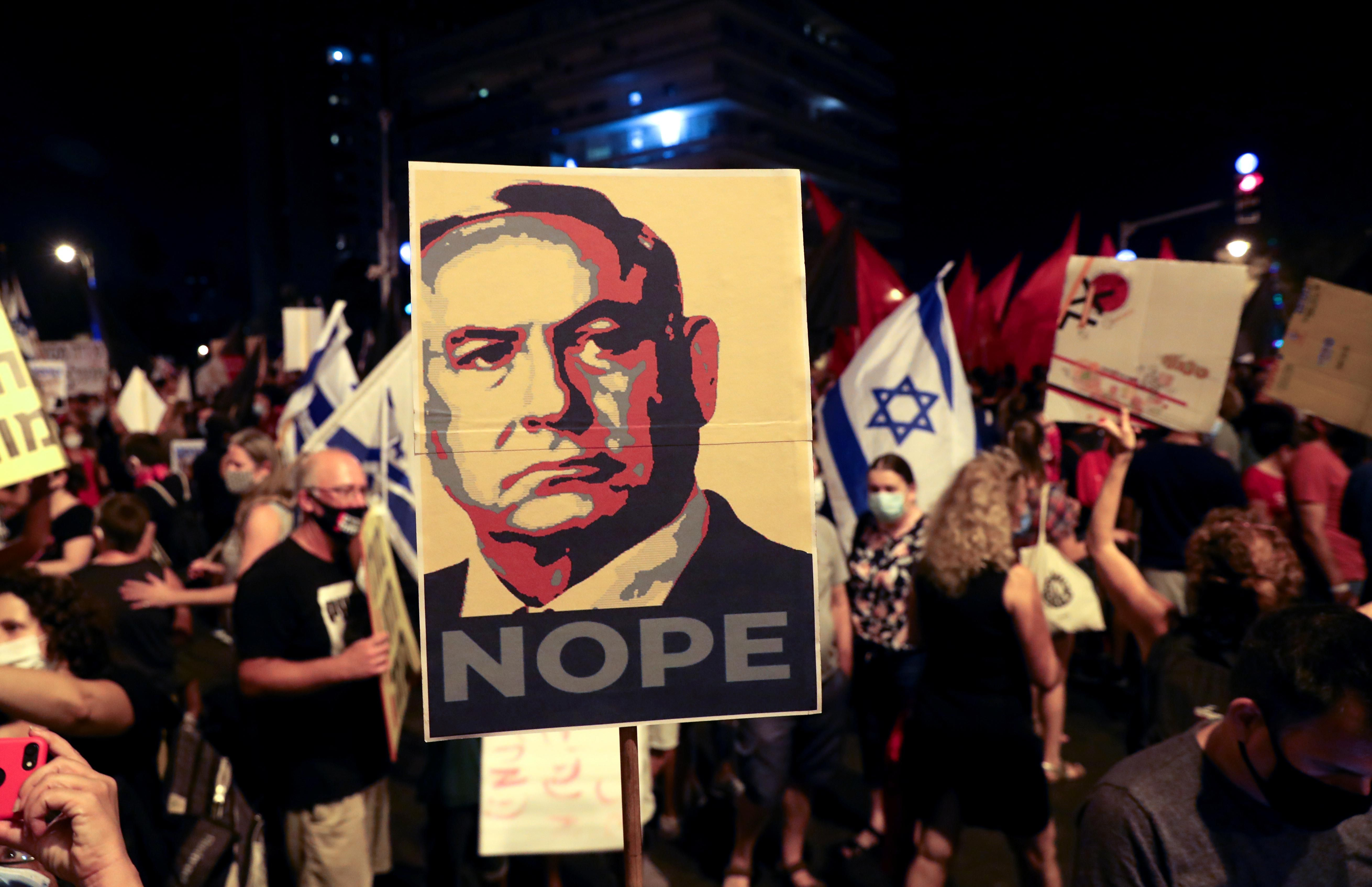 """Protesters holding an image of Israel's Prime Minister Benjamin Netanyahu pasted with the slogan """"NOPE"""""""