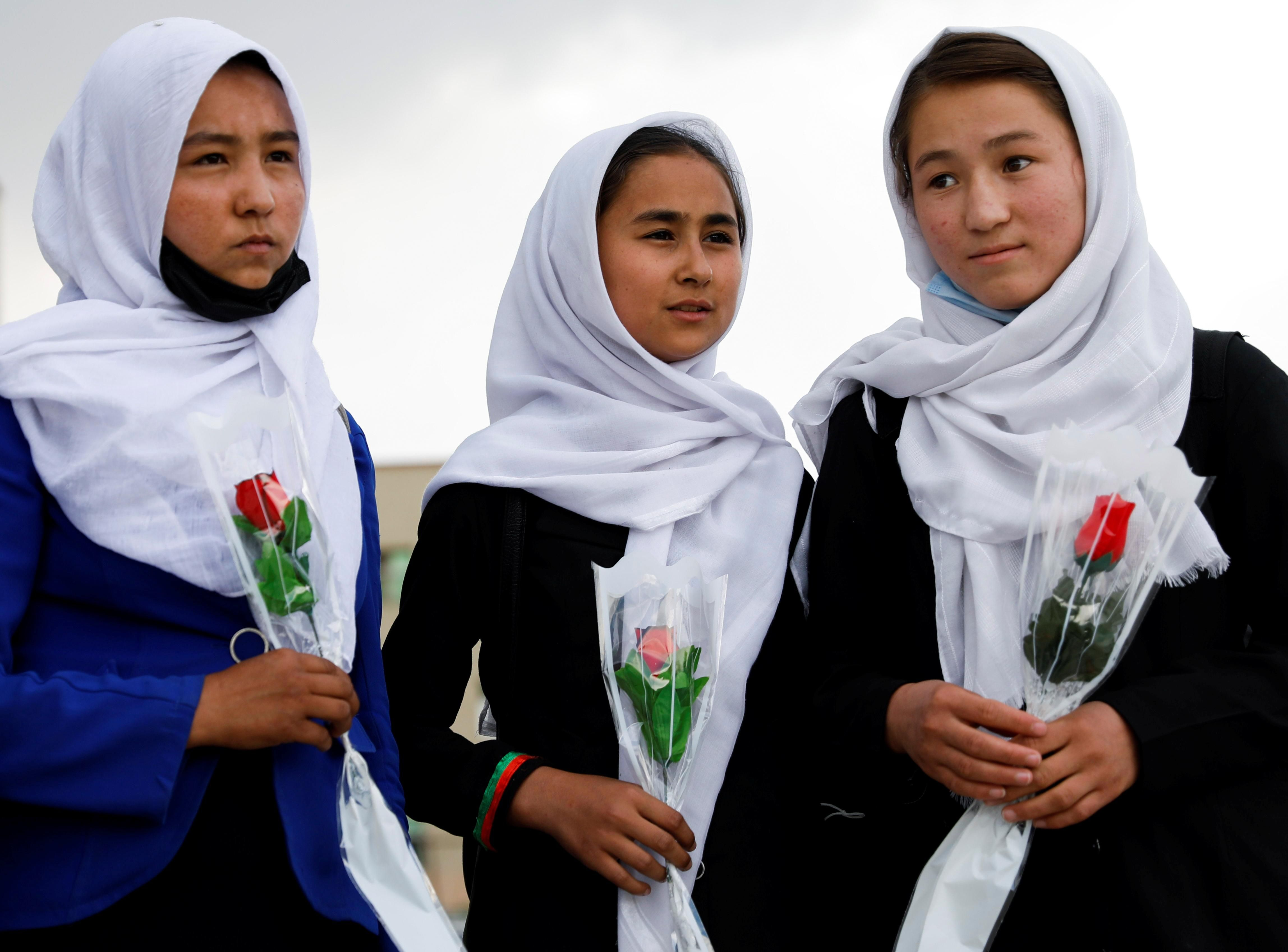 Schoolgirls hold flowers as they arrive to visit students who were injured in a car bomb blast outside a school, at a hospital in Kabul, Afghanistan May 10, 2021.