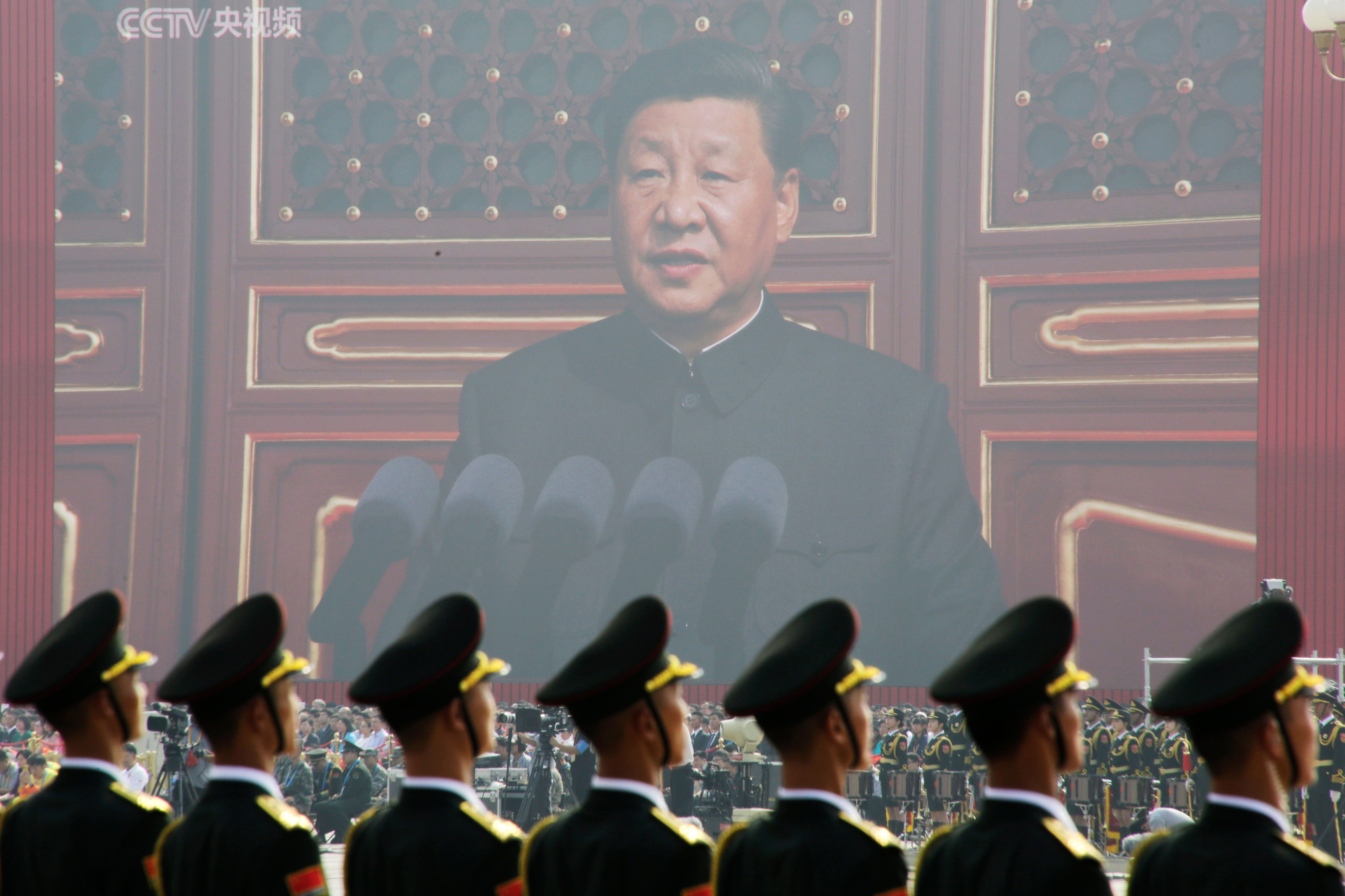 Soldiers of People's Liberation Army (PLA) are seen before a giant screen as Chinese President Xi Jinping speaks at the military parade marking the 70th founding anniversary of People's Republic of China
