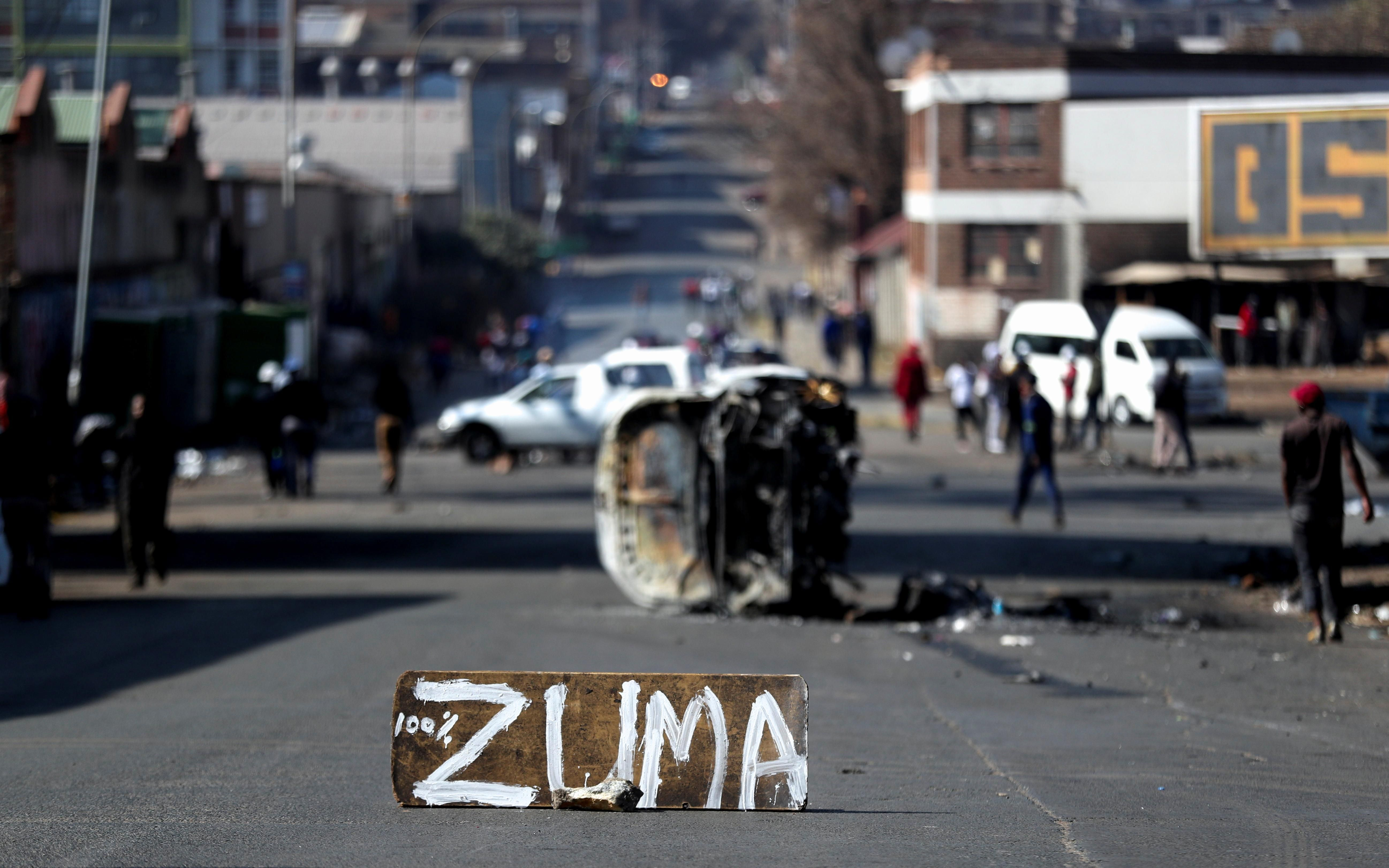 The remains of a burnt car and a sign block the road after stick-wielding protesters marched through the streets, as violence following the jailing of former South African President Jacob Zuma spread to the country's main economic hub in Johannesburg, South Africa, July 11, 2021