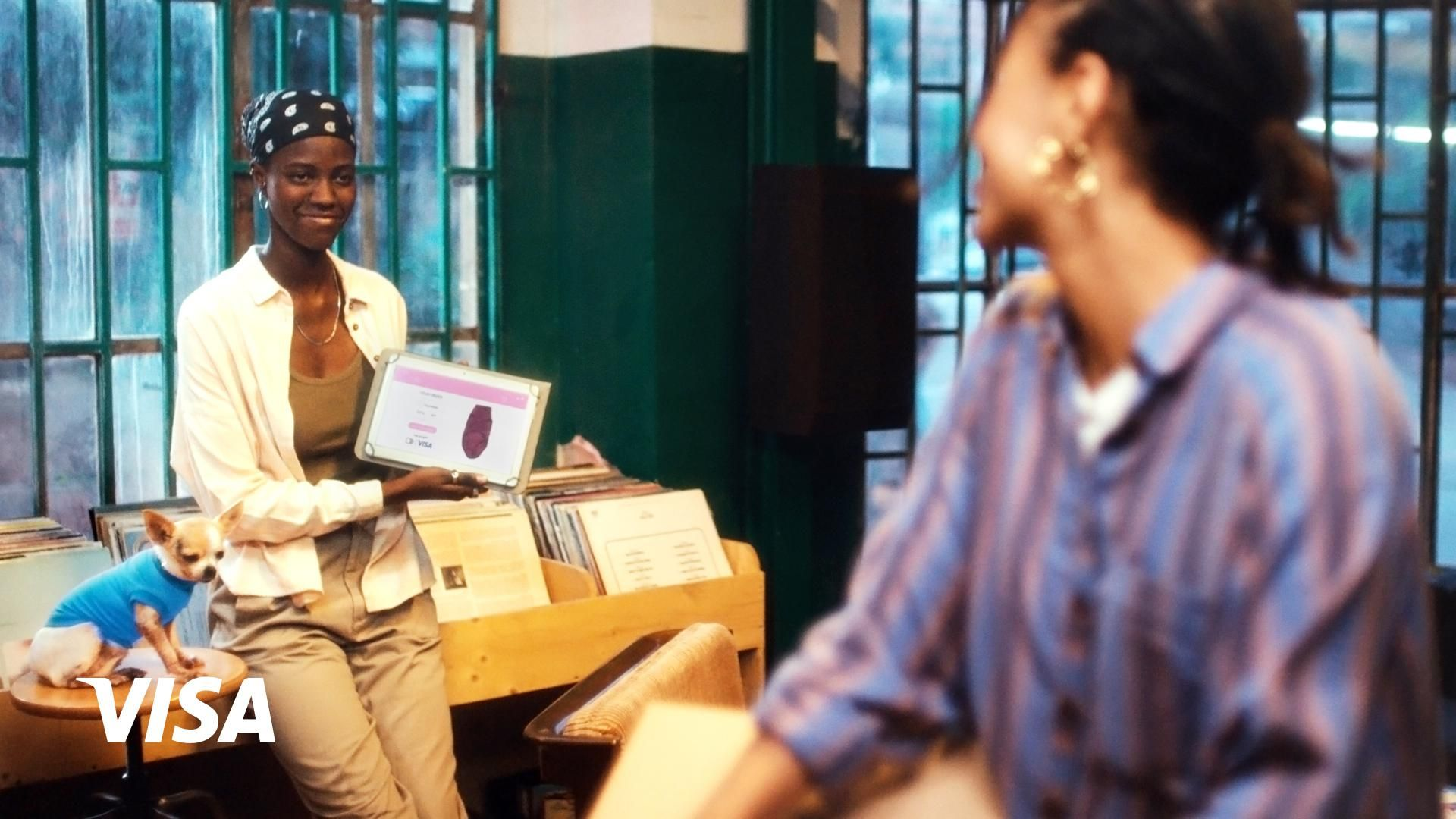Two Black women looking at one another across a record store, one showing a screen displaying an online Visa purchase