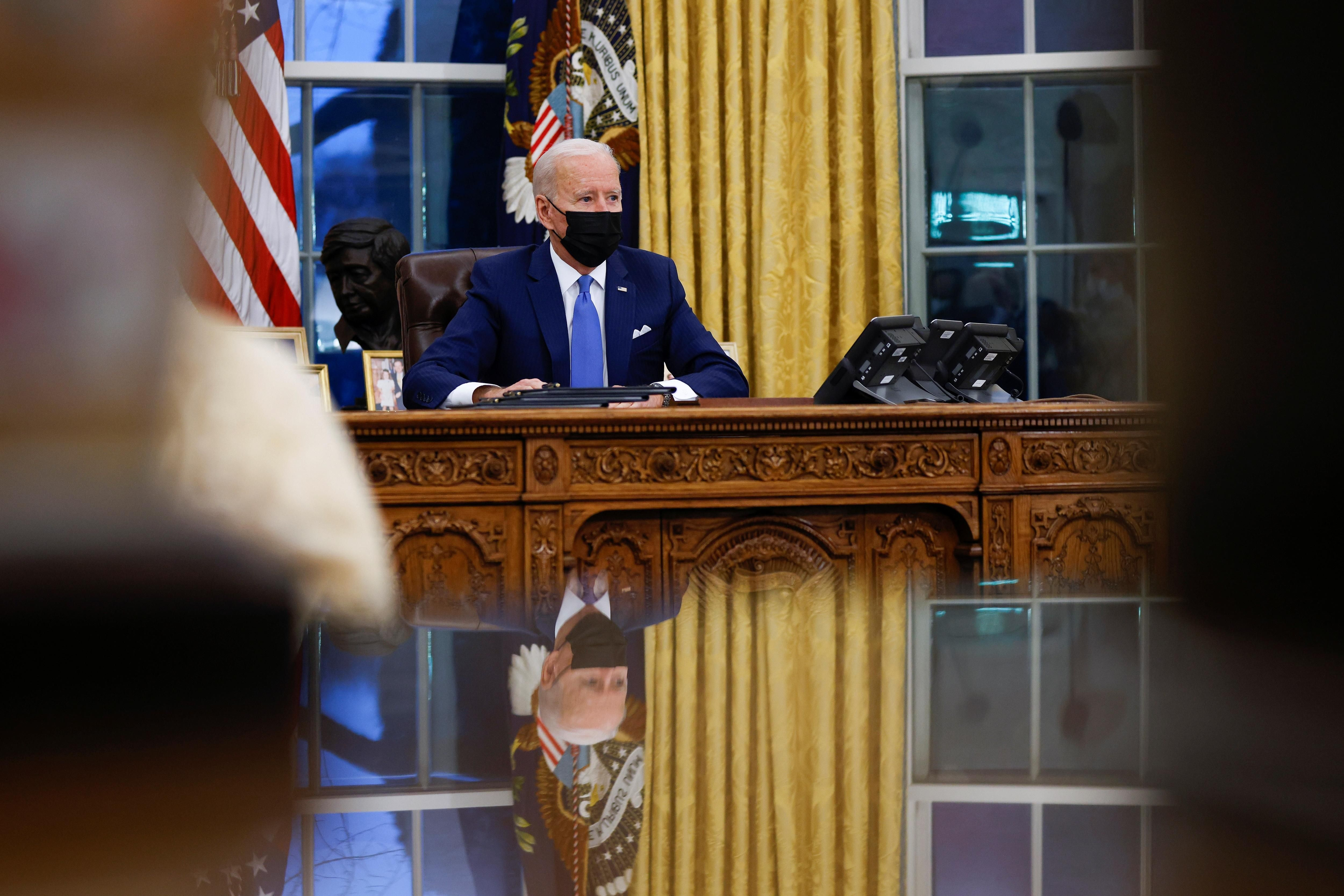 U.S. President Joe Biden signs executive orders on immigration reform inside the Oval Office at the White House in Washington, U.S., February 2, 2021.