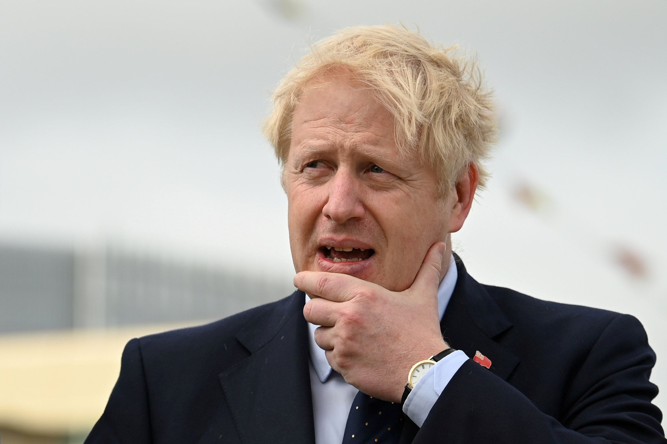 UK Prime Minister Boris Johnson with a hand to his chin looking concerned
