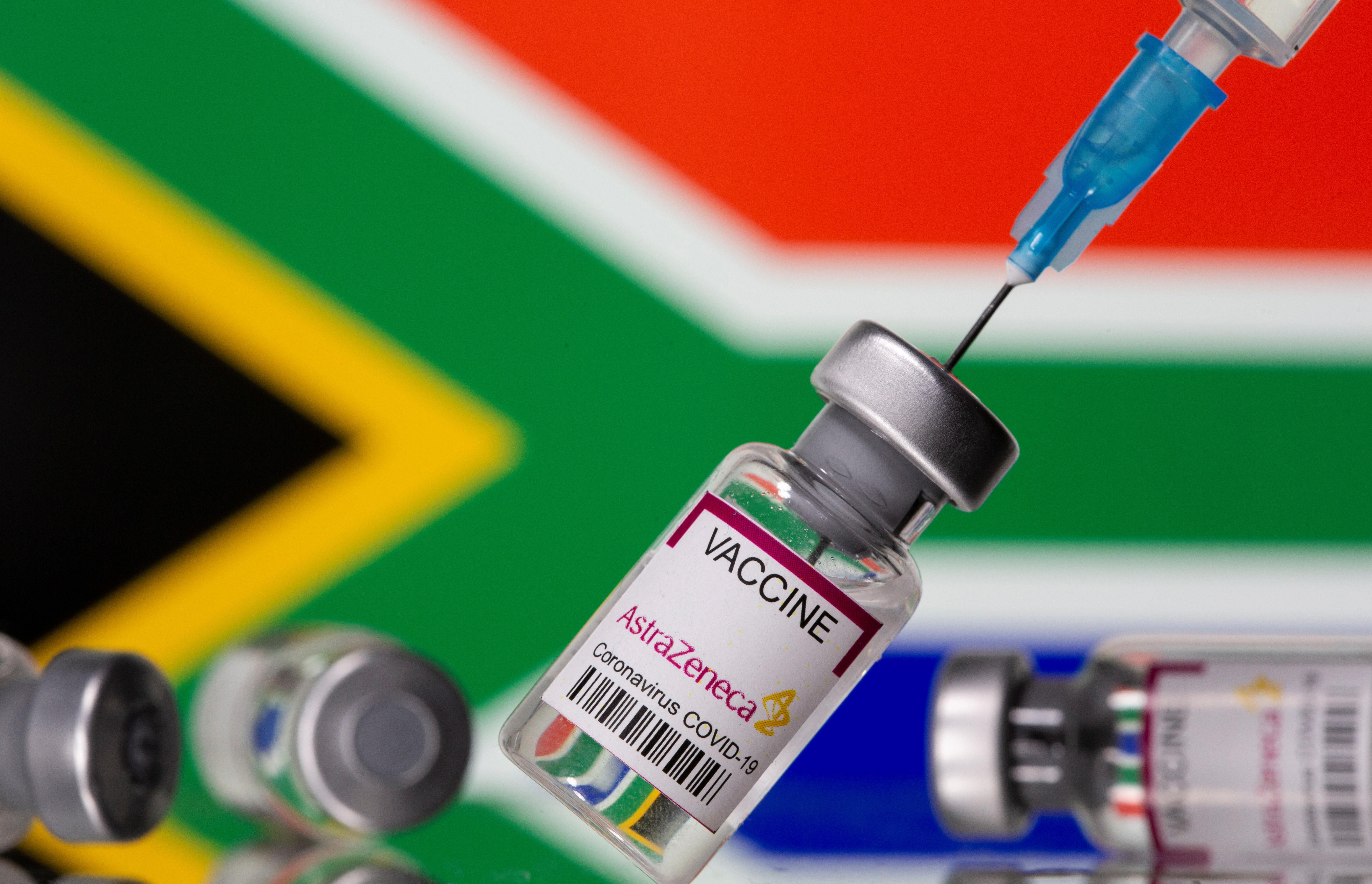 """Vials labelled """"Astra Zeneca COVID-19 Coronavirus Vaccine"""" and a syringe are seen in front of a displayed South Africa flag, in this illustration photo taken March 14, 2021."""